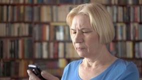 Moderne hogere vrouw die thuis cellphone, het doorbladeren, het lezen gebruiken Boekenkastboekenrekken op achtergrond stock videobeelden