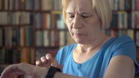 Moderne hogere vrouw die thuis smartwatch, het doorbladeren, het lezen gebruiken Boekenkastboekenrekken op achtergrond stock videobeelden