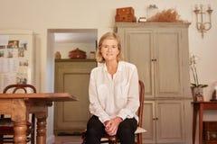 Moderne hogere vrouwenzitting in haar rustiek stijlhuis royalty-vrije stock afbeeldingen