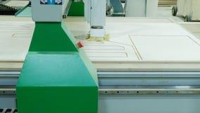 Moderne houtbewerkingsmachine in actie Besnoeiingen krullende stukken van triplexblad Productie van houten meubilair royalty-vrije stock afbeelding
