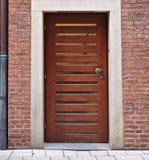Moderne houten deur in rode bakstenen muur met smalle horizontale ruiten en downspout royalty-vrije stock afbeeldingen
