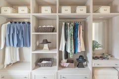 Moderne houten garderobe met kleren die op spoor in gang in c hangen royalty-vrije stock afbeeldingen