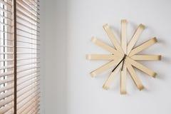 Moderne houten klok op witte muur naast venster met zonneblinden in eenvoudig vlak binnenland Echte foto royalty-vrije stock foto