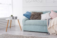 Moderne houten koffietafel en comfortabele bank met hoofdkussens Het decorconcept van het woonkamer binnenlands en eenvoudig mode stock foto's