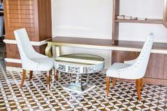Moderne Innenarchitektur einer Hotellobby mit weißen Stühlen und Spiegeltabelle stockbild