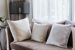 Moderne Innenkissen auf braunem Sofa Stockbild