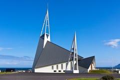 Moderne Island-Kirche auf hellem Hintergrund des blauen Himmels Stockbild