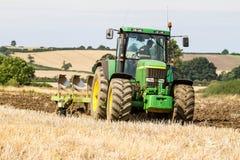 Moderne John Deere-tractor die een ploeg trekken Royalty-vrije Stock Afbeeldingen