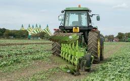 Moderne John Deere-tractor die een ploeg trekken Stock Afbeelding