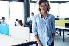 Moderne jonge Afrikaanse bedrijfsvrouw in het bureau met exemplaarruimte stock foto's