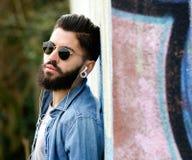 Moderne jonge mens die met baard aan muziek met oortelefoons luisteren royalty-vrije stock afbeelding