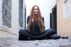 Moderne jonge vrouwenzitting in de straat stock afbeeldingen