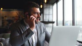 Moderne jonge zaken die telefoongesprek hebben tijdens de koffiepauze stock footage