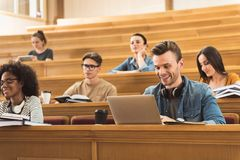 Moderne jongeren die in lezingszaal bestuderen stock afbeeldingen
