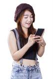 Moderne Jugendliche, die mit einem Smartphone simst Stockbild