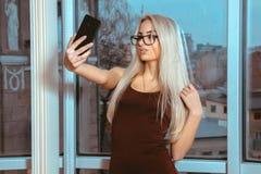 Moderne junge blonde Dame macht selfie am Fenster mit Ci Stockbild