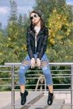 Moderne junge Frau in der Felsenartkleidung, schwarze Lederjacke, Blue Jeans, Strumpfhosen in einem Gitter unter zerschlagenen Je Stockfotografie