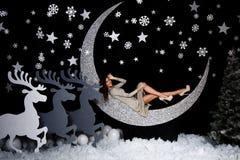 Moderne junge Frau in der Festtagskleidung, die im Studio mit Weihnachtsdekorationen aufwirft lizenzfreies stockfoto