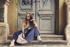 Moderne junge Frau, die auf der Treppe im langen Kleid sitzt stockbilder