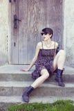 Moderne junge Frau, die auf Treppen sitzt Lizenzfreies Stockfoto