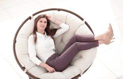 Moderne junge Frau, die im bequemen runden Stuhl sitzt lizenzfreie stockbilder