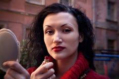 Moderne junge gelockte Frau über ausrangierter dunkler Wand stockbild