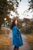 Moderne junge gelockte Frau im Herbst in lächelndem und Drehentragendem blauem Mantel des Parks stockfoto
