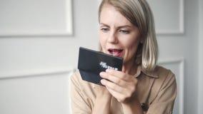 Moderne junge Geschäftsfrau mit perfekter Hautpflege und dem Reparieren ihres Makes-up unter Verwendung des kleinen Spiegels, wäh stock footage