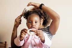 Moderne junge glückliche Afroamerikanerfamilie: bemuttern Sie Tochterhaar zu Hause kämmen, Lebensstilleutekonzept Stockfotografie