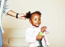Moderne junge glückliche Afroamerikanerfamilie: bemuttern Sie Tochterhaar zu Hause kämmen, Lebensstilleutekonzept Lizenzfreie Stockbilder
