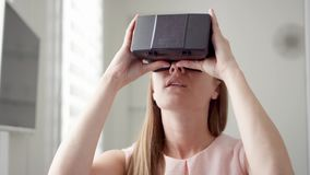 Moderne junge hübsche Frau, die zu Hause VR-virtuelle Realität 360 Gläser verwendet Zukunft ist weibliches Konzept stock video
