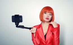 Moderne junge Rothaarigefrau im roten Herstellungsselfie mit einem Stock lizenzfreies stockfoto