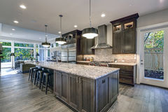 Moderne Küche mit braunen Küchenschränken stockbilder