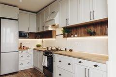 Moderne Küchenluxusmöbel in der grauen Farbe und im Stahlofen, Kühlschrank, Wanne, hölzerne Tischplatte, Töpfe, Graue Kabinette a lizenzfreie stockbilder