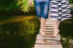 Moderne kühle Paare auf einer Brücke nahe dem Wasser, Verhältnisse, Romance, Beine, Lebensstil - Konzept Stockfotos