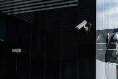 Moderne kabeltelevisie-camera op een muur Een vage nachtcityscape achtergrond Concept toezicht en controle Gestemd beeld stock foto's