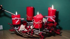 Moderne Kerstmiskroon met vier rode kaarsen op houten oppervlakte met groene achtergrond stock footage