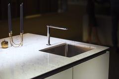 Moderne keuken, de waterkraan en de keukengootsteen Keukeneiland met een kraan en een marmeren witte worktop stock afbeeldingen