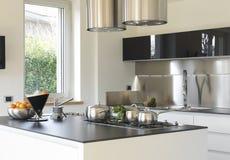 Moderne keuken met staalpannen Stock Afbeeldingen