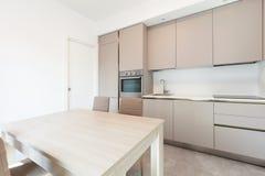 Moderne keuken in totale witte flat stock afbeelding