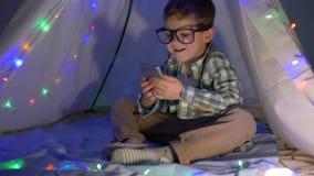 Moderne Kindheit, glückliches Kind untersucht den Smartphone, der zu Hause in einem Wigwamdekor mit Girlande sitzt stock video