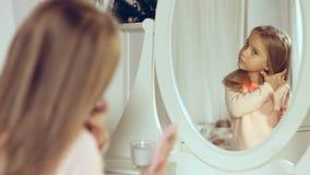 Moderne kleine Dame, die ihr Haar kämmt und im Spiegel schaut Lizenzfreies Stockbild
