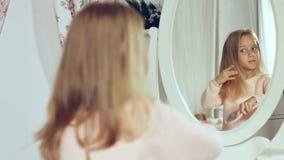 Moderne kleine Dame, die ihr Haar kämmt und im Spiegel schaut Stockfoto