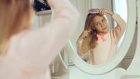 Moderne kleine Dame, die ihr Haar kämmt und im Spiegel schaut Stockbilder