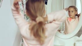 Moderne kleine Dame, die ihr Haar kämmt und im Spiegel schaut Stockfotos