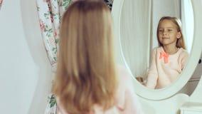 Moderne kleine Dame, die ihr Haar kämmt und im Spiegel schaut Stockfotografie