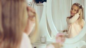 Moderne kleine Dame, die ihr Haar kämmt und im Spiegel schaut Stockbild