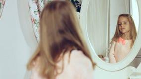 Moderne kleine Dame, die ihr Haar kämmt und im Spiegel schaut Lizenzfreie Stockfotografie