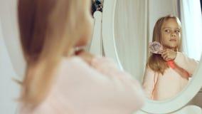 Moderne kleine Dame, die ihr Haar kämmt und im Spiegel schaut Lizenzfreie Stockfotos