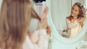 Moderne kleine Dame, die ihr Haar kämmt und im Spiegel schaut Lizenzfreie Stockbilder